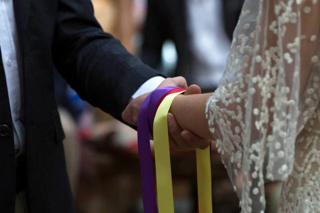 A groom holding the hand of a bride